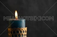 Teal candle with straw twigged holder trembling flame close up out of the grey background, off-center, blown out