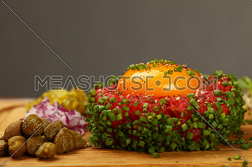 One portion of raw minced beef meat tartare steak with egg yolk, green chive, onions and capers on wooden board, close up, low angle view