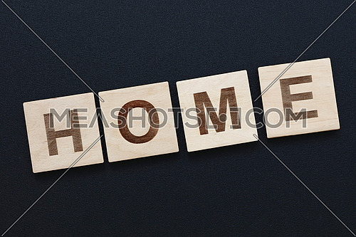 Close up word HOME on wooden scrabble letter signs over black board background