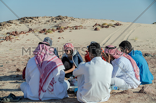 Group of tourists sitting with bedouin guides exploring Sinai Trail from Ain Hodouda at day.
