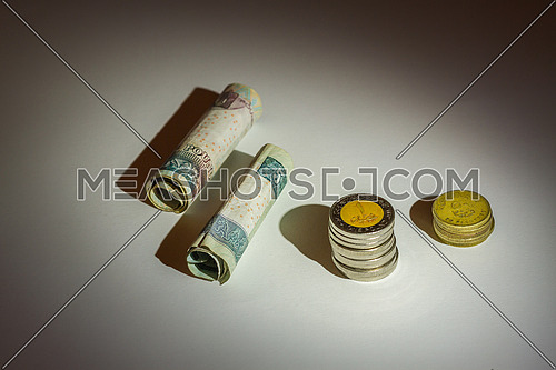 Egyptian Money rolled banknotes and coins on a grey table top under spotlight