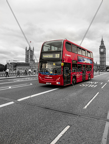 The famous London bus on the famous London bridge beside Big Ben and the Parliament Houses.