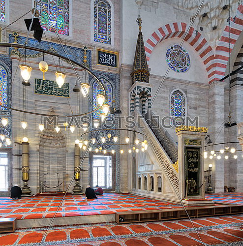 Istanbul, Turkey - April 19, 2017: Marble floral golden ornate minbar (Platform) and niche, with few prayers at Suleymaniye Mosque, Istanbul, Turkey