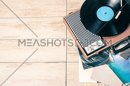 Gramophone with a vinyl record on wooden table, top view and copy space,photo desaturate and split toning for old style.