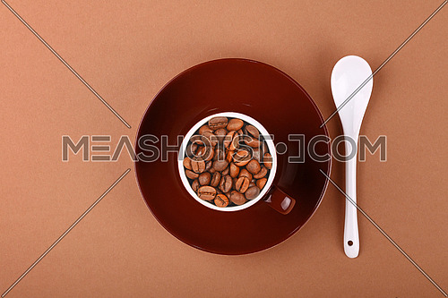 Small brown ceramic espresso cup full of roasted coffee beans, with saucer and white spoon on paper parchment, close up, elevated top view, directly above