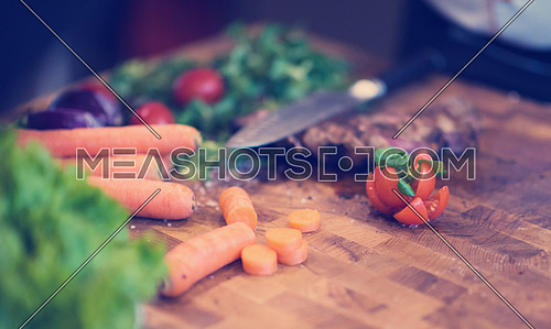Juicy slices of grilled steak  with vegetables on a wooden board