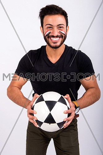 A young man encourages the Egyptian football team paints the flag of Egypt on his face