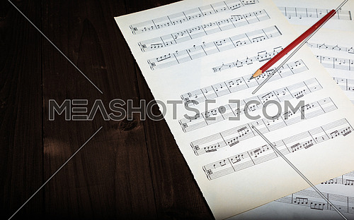 In the picture aged pages of sheet music, pencil  and wooden background.