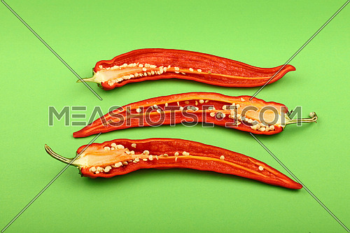 Three cut halves of fresh red hot chili peppers on green paper background, close up, elevated high angle view