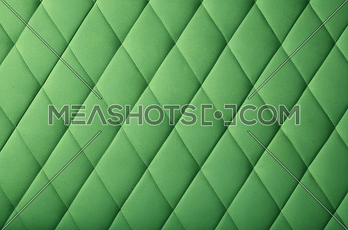 Background texture of pastel dark green genuine leather soft tufted furniture or wall panel upholstery with deep diamond pattern, close up