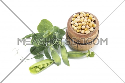 Dried peas in a wooden barrel and fresh plant with pods isolated on a white background