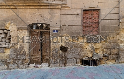 Grunge stone bricks wall with Broken wooden door and closed broken window in abandoned Darb El Labana district, Cairo, Egypt