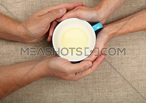 Man and woman hands holding and hugging together big empty cup of green tea over canvas tablecloth, close up, elevated top view