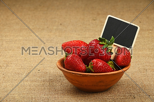 Fresh mellow red strawberries in rustic ceramic bowl with chalk blackboard price tag sign on jute burlap canvas background