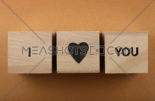 Wooden cube signs with I LOVE YOU words over background of brown kraft paper with copy space, elevated top view, directly above