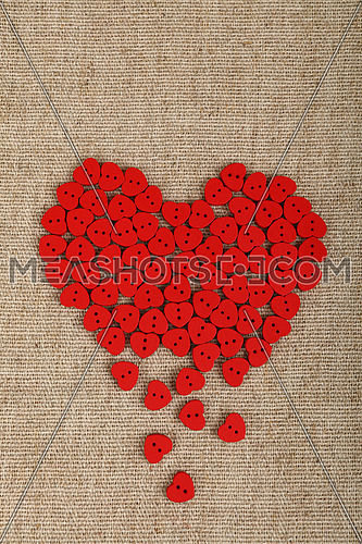 Red heart shaped handmade wooden sewing buttons form broken heart on linen canvas with copy space left, elevated top view