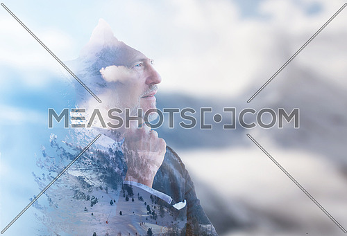 Double exposure of senior businessman in front of the big  mountain