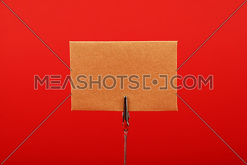 Blank brown kraft cardboard paper parchment sign with copy space on metal note holder over red background, front side view