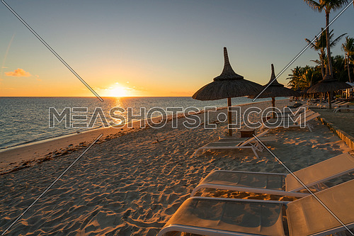 Amazing sunset, sandy beach with deckchairs and parasols typical of the Mauritius resorts