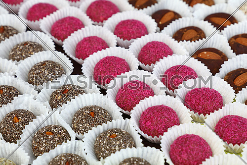 Close up selection of assorted sweet candy cookies in white paper cups at retail bakery shop, high angle view