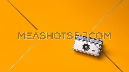 Old vintage Photo Camera on a yellow Background