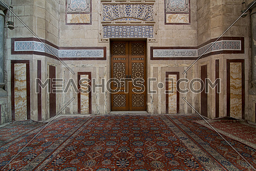 Interior shot of Al Rifaii Mosque (Royal Mosque) with decorated marble wall and ornate wooden door, located in front the Cairo Citadel, Cairo, Egypt