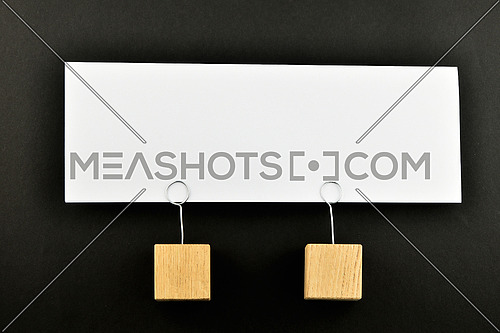 Together, One big white paper note with two wooden holders isolated on black paper background for presentation
