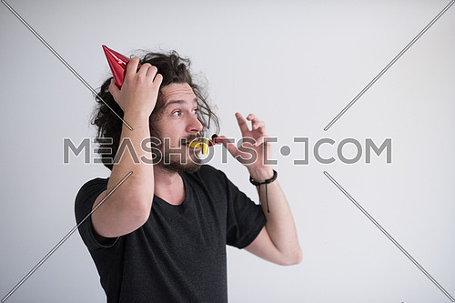 Portrait of a man in party hat blowing in whistle isolated on a white background
