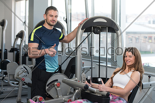 Young Woman Doing Aerobics Leg Exercise On Machine In Gym And Personal Trainer Watching On Her