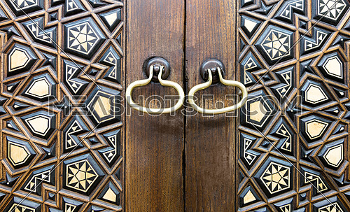 Closeup of two golden ring door knobs over an aged decorated wooden door, Medieval Cairo, Egypt
