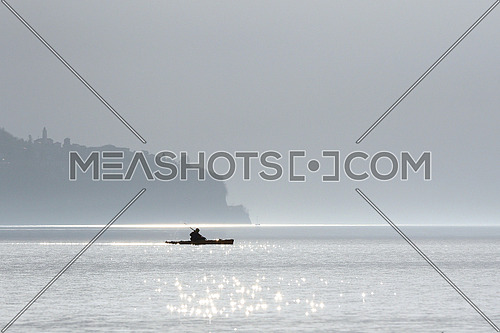 Kayak crossing Lake Maggiore on a hazy winter day in the swiss Alps