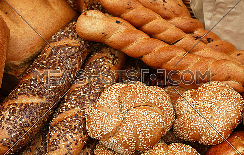 Close up several assorted fresh wheat bread buns, loaves and baguettes on retail display of bakery store, high angle view