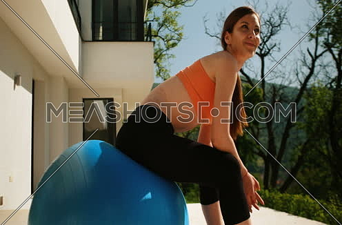 Young Woman Doing Yoga and streching on ball in front of villa