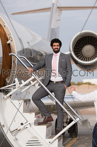 Portrait of a young middle eastern successful businessman at the airport entering the private plane