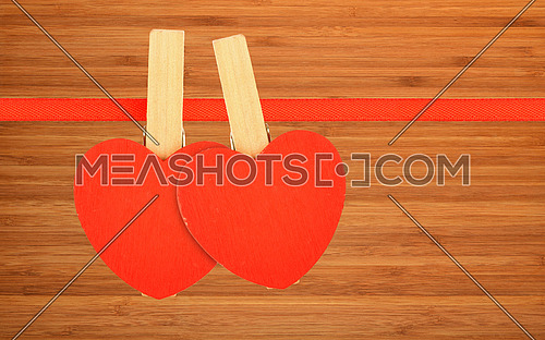 Valentine day template, two red wooden hearts with clothes pins on textile ribbon over bamboo wood board surface