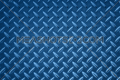 Background of dark blue toned industrial anti slip embossed metal steel plate with classic diagonal bumps of diamond pattern texture, close up