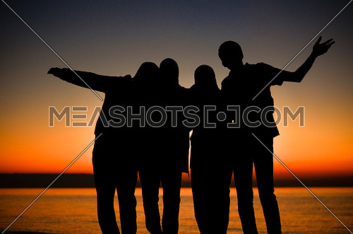 A Four group of friends enjoying their time and having fun , making memories by the beach at sunset time