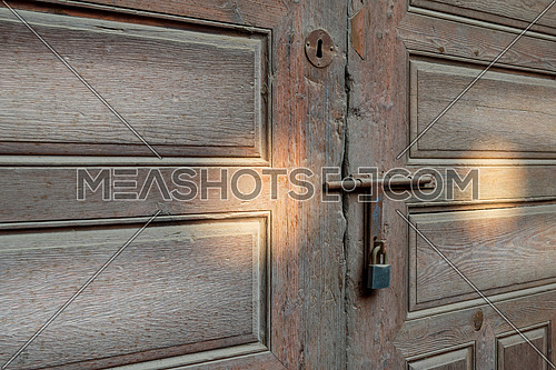 Closeup of rusted metal aged latch and padlock over weathered wooden door