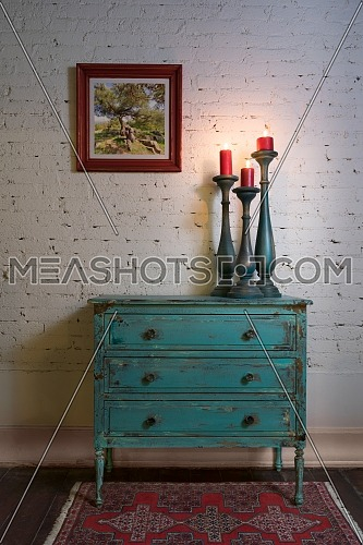Retro composition of Green vintage cabinet, candlesticks with lighted candles and hanged painting on white bricks wall in studio
