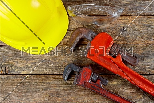 Safety leather gloves building helmet and glasses tool on wooden board construction concept