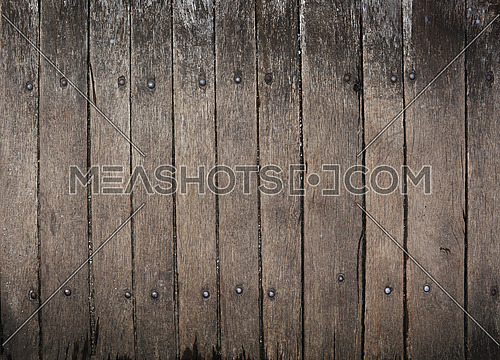 Vintage dark brown wooden vertical planks background texture with scratches, woodgrain stains and black joints, close up