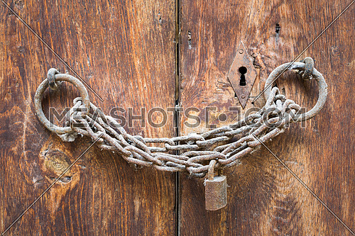 Old rusted padlock, rusted chain, and keyhole on a closed wooden aged grunge double door