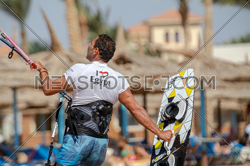 Kite Surfer waling on beach wearing surfing set by day.