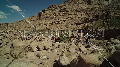 Reveal shot for group of tourists walking on big rocks with bedouin guide to explore Sinai Mountain for wadi Freij at day.