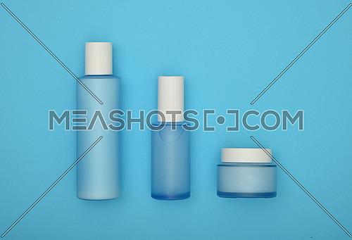 Close up set of three cosmetic skin care cream, lotion and tonic bottles over pastel blue background, elevated top view, directly above