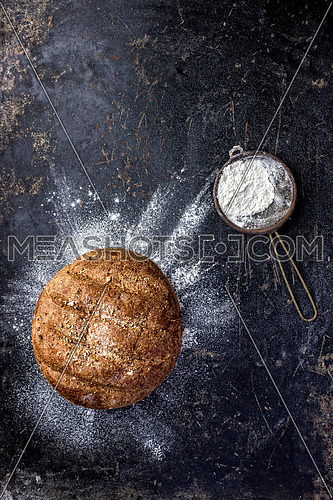 bread and flour on a black counter top