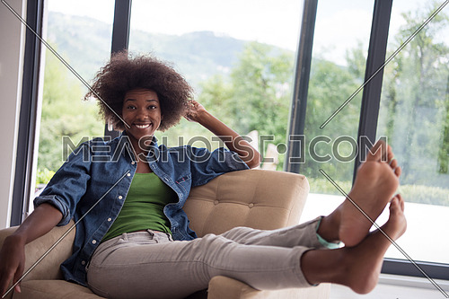 Young african american woman at home in the chair relaxing in her luxury home