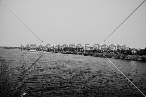 A landscape of the Nile river water and sand mountains by the shore and plants in black and white