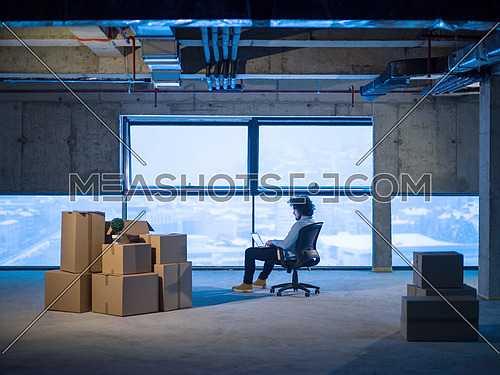 young male architect on construction site checking documents and business workflow using laptop computer with cardboard boxes around him in new startup office