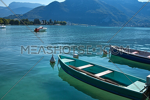 Close up empty pleasure launch boats in turquoise lake water, high angle view, sunny day in Annecy, France